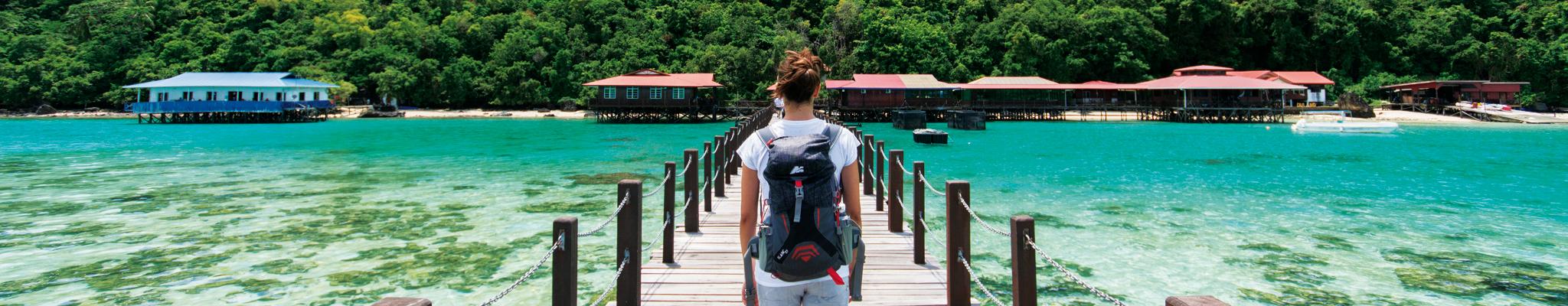Ragazza che cammina su un pontile a Bohey Dulang Island con zaino Blanc 25